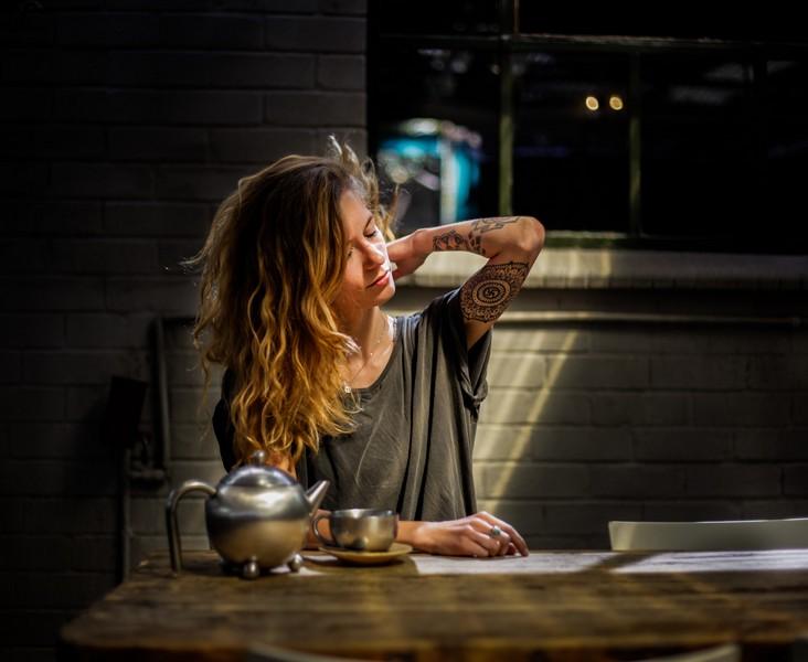 femme dans sa cuisine qui boit un café et se touche le cou