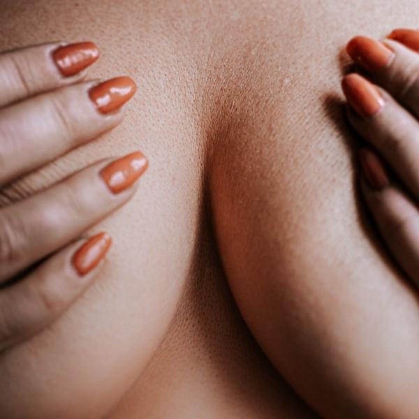 seins d'une femme cachés par ses mains