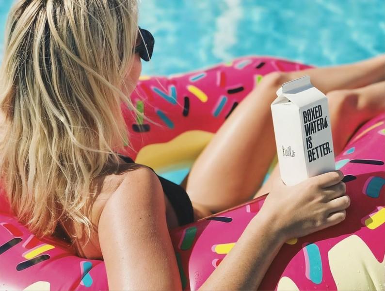 femme installée dans une bouée dans une piscine qui sirote un bouteille d'eau