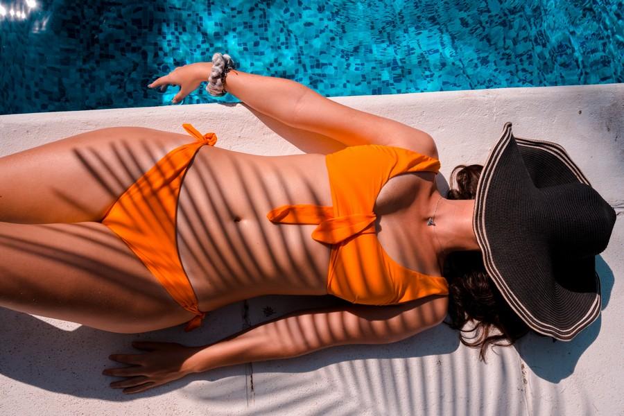 femme qui bronze en maillot de bain près d'une piscine avec son chapeau sur la tête
