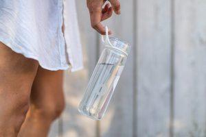 femme qui tient une gourde d'eau