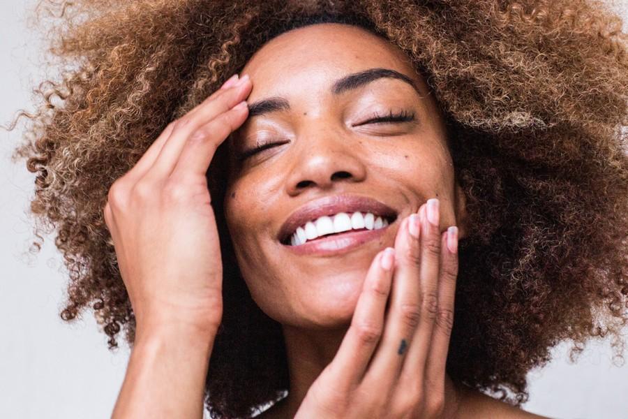 femme aux cheveux crépus qui sourit et se touche le visage