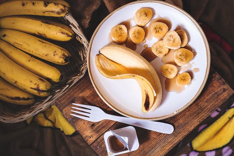 assiette avec de la banane en morceaux et le fruit entier