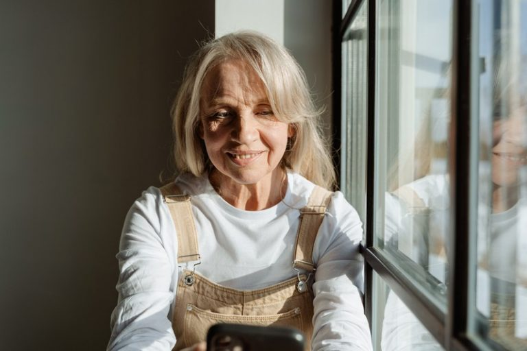 femme de plus de 55 ans assise à côté de la fenêtre