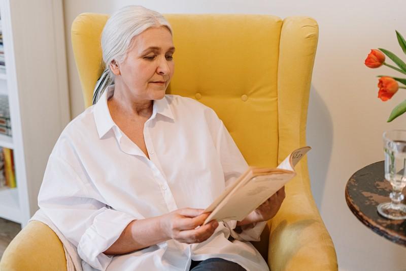femme senior qui lit sur un fauteuil